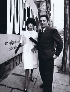 Federico Fellini in New York. Poster of his film La Dolce Vita and model wearing a Simonetta coat.